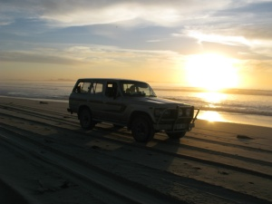 A battered old 4WD cruises along the beach at sunset near  lake Alexandrina